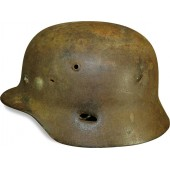 ET 64 marked M 35 war time reissued camouflaged steel helmet with fragmentation damage