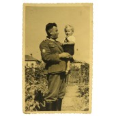 German Wehrmacht Gebirgsjager posing with a child at the  Russian backyard.