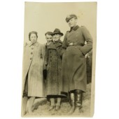 German officer in overcoat and visor hat with family